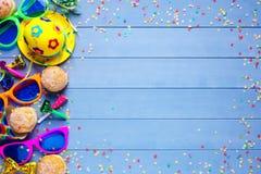 Bunte Geburtstags- oder Karnevalsgrenze mit Parteieinzelteilen auf hölzernem Hintergrund Lizenzfreie Stockfotografie