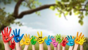 Bunte gemalte Hände vor einer Frühlingsszene Stockfotografie
