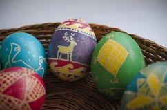 Bunte gemalte Ostereier in einem gesponnenen Strohkorb Lizenzfreies Stockfoto