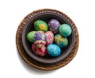 Bunte gemalte Ostereier in einem gesponnenen Strohkorb auf weißem Hintergrund Lizenzfreie Stockfotografie