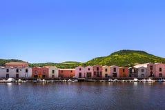 Bunte Gerbereihäuser auf einem Kanal mit Booten und grünem Gebirgszug im Hintergrund, Bosa, Sardinien, Italien stockfotografie