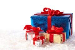 Bunte Geschenkkästen auf dem Schnee getrennt auf Weiß Lizenzfreies Stockfoto