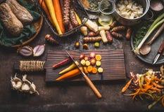 Bunte geschnittene Karotten mit Messer auf hölzernem Schneidebrett auf rustikalem Küchentischhintergrund mit Wurzelgemüsebestandt stockbild