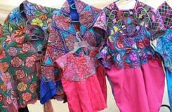 Bunte gestickte Kleider am mexikanischen Handwerksmarkt Lizenzfreie Stockbilder