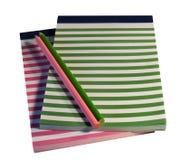 Bunte gestreifte Notizblöcke und Bleistifte Stockbild