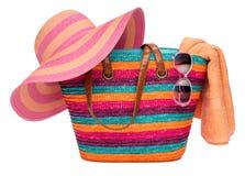 Bunte gestreifte Strandtasche mit einem Strohhuttuch und -Sonnenbrille Stockfotos