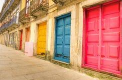 Bunte getragene gemalte Türen entlang Straße in Porto Stockfoto