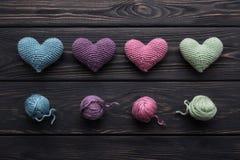 Bunte gewirkte Herzen u. Stränge auf grauer hölzerner Tabelle Stockbild