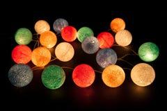 Bunte glühende Bälle auf einem schwarzen Hintergrund Glühende Girlande nachts Bunte Kreise auf dem Hintergrund Stockbilder