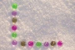 Bunte Glasweihnachtsbälle auf dem glänzenden Schneehintergrund stockfotos