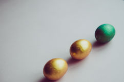Bunte grüne und goldene Ostereier mit dem Süßigkeitenbesprühen Stockfotos