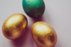 Bunte grüne und goldene Ostereier mit dem Süßigkeitenbesprühen Lizenzfreie Stockfotografie