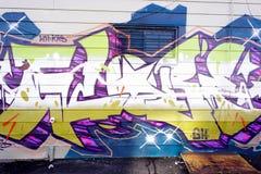 Bunte Graffiti auf einer Backsteinmauer Stockbild