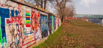 Bunte Graffiti legen an Graben nahe einer Brücke Steine in den Weg lizenzfreies stockfoto
