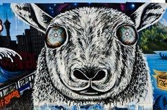 Bunte Graffiti-Schafe auf der strukturierten Backsteinmauer Stockbilder