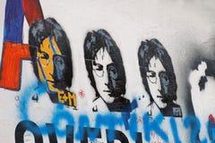 Bunte Graffitiwand, drei Kopien von Lennon Stockfotos