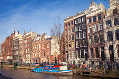 Bunte Häuser entlang dem sonnigen Tag des Kanals im Frühjahr, Amsterdam Stockfotografie
