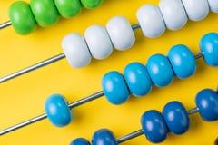 Bunte hölzerne Abakusperlen auf gelbem Hintergrund, dem Geschäft finanziell oder den Istkosten und Ausgabenberechnungskonzept ode stockfotos