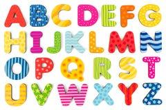 Bunte hölzerne Alphabetbuchstaben auf einem weißen Hintergrund