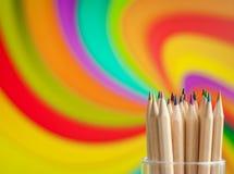 Bunte hölzerne Bleistifte auf buntem Hintergrund Stockfotos