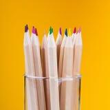 Bunte hölzerne Bleistifte auf gelbem Hintergrund Stockfotos