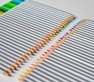 Bunte hölzerne Bleistifte, die in Folge lokalisiert auf weißem Hintergrund liegen lizenzfreie stockbilder