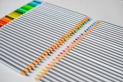 Bunte hölzerne Bleistifte, die in Folge lokalisiert auf weißem Hintergrund liegen Lizenzfreies Stockfoto