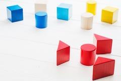 Bunte hölzerne geometrische Bausteine auf weißem hölzernem backgr Stockfoto