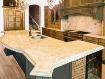 Bunte hölzerne Küchenschränke mit Geräten, Granit Countertops und Massivholzboden stockfotografie