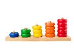 Bunte hölzerne Kinder spielen Ergebnisse von einem bis fünf Zahlen der farbigen Ringe, die auf einem weißen Hintergrund lokalisie Stockfoto