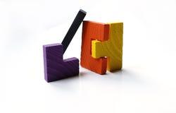 Bunte hölzerne Puzzlespielblöcke auf weißem Hintergrund Lizenzfreies Stockfoto