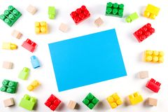 Bunte hölzerne Würfel und Plastikbaublöcke mit blauer Karte des leeren Papiers auf weißem Hintergrund Lizenzfreie Stockfotografie