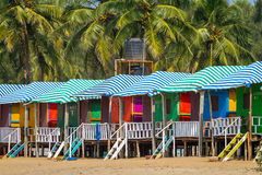 Bunte Hütten auf dem sandigen Strand in Goa lizenzfreies stockbild