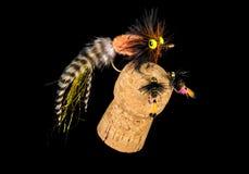 Bunte Hand gebundene Fischen-Fliegen angezeigt auf Champagne Cork 11 Stockfotos