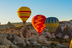 Bunte Heißluft steigt das Fliegen über Felsenlandschaft bei Cappadoc im Ballon auf lizenzfreies stockfoto