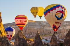 Bunte Heißluft steigt das Fliegen über Felsenlandschaft bei Cappadoc im Ballon auf stockfotografie