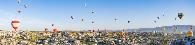 Bunte Heißluft steigt das Fliegen über Felsenlandschaft bei Cappadocia die Türkei im Ballon auf lizenzfreies stockbild