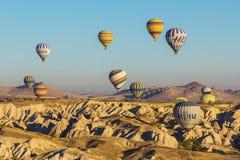 Bunte Heißluft steigt das Fliegen über Felsenlandschaft im Ballon auf stockbilder