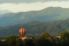 Bunte Heißluftballone, die über den Berg fliegen Lizenzfreies Stockbild