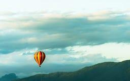 Bunte Heißluftballone, die über den Berg fliegen Stockbild