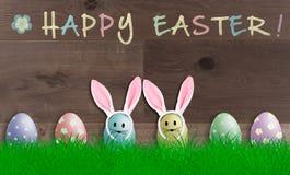 Bunte helle Pastell-Ostereier mit den Häschenohren auf hölzernem Hintergrund, förderndes Zeichen mit Text fröhliche Ostern lizenzfreie stockfotografie
