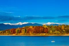 Bunte Herbstlandschaft mit See und einem Boot Lizenzfreies Stockfoto