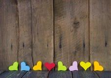 Bunte Herzen auf hölzernem Hintergrund für eine Grußkarte. Lizenzfreies Stockbild
