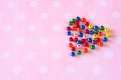 Bunte Herzform gemacht von den Perlen auf rosa Weinlesehintergrund Stockbilder