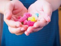Bunte Herzsüßigkeit auf Frauenhänden für Valentinsgrußhintergrund lizenzfreie stockfotos