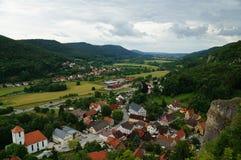 Bunte historische Stadt in einem grünen Tal, das durch einen Fluss gekennzeichnet wird und Felder in einem Karst gestalten landsc lizenzfreie stockfotos