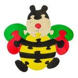 Bunte hölzerne Puzzlespielstücke in der Bienenform Stockbild