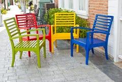 Bunte Holzstühle auf verschiedenem Hintergrund Stockfotos