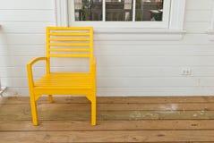 Bunte Holzstühle auf verschiedenem Hintergrund Stockfotografie