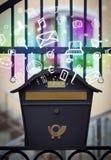 Bunte Ikonen und Symbole, die aus einem Briefkasten heraus bersten Stockfoto
